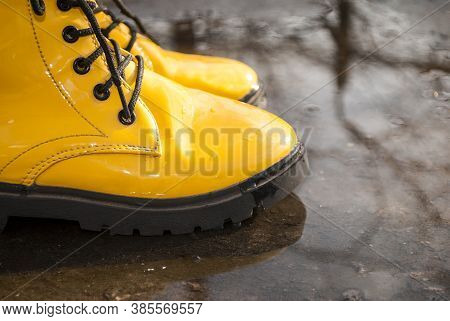 Bright Yellow Rubber Boots Standing In A Puddle. Boots With A Massive Sole Of A Tractor Of Black Col