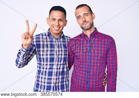 Young gay couple of two men wearing casual clothes showing and pointing up with fingers number two while smiling confident and happy.