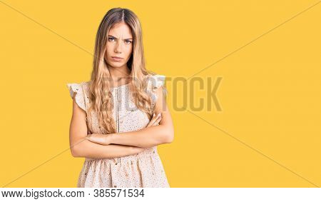Beautiful caucasian woman with blonde hair wearing elegant summer clothes skeptic and nervous, disapproving expression on face with crossed arms. negative person.