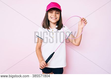 Young little girl with bang holding badminton racket winking looking at the camera with sexy expression, cheerful and happy face.