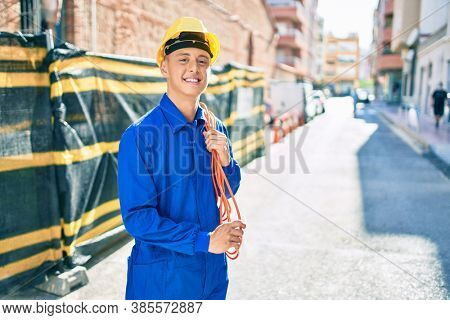 Young hispanic workman smiling happy holding electrical cable at street of city