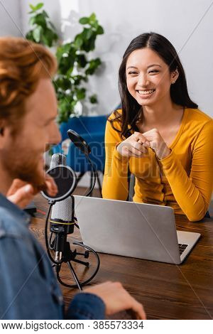 Selective Focus Of Excited Asian Interviewer Looking At Guest In Radio Studio