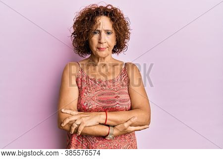 Beautiful middle age mature woman wearing summer dress skeptic and nervous, disapproving expression on face with crossed arms. negative person.