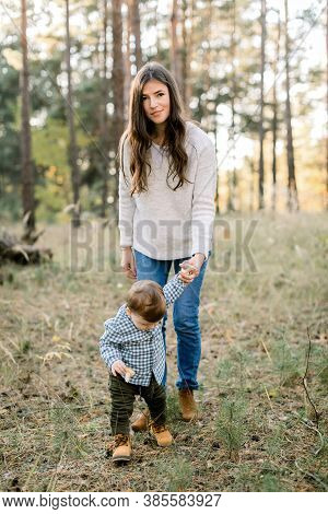 First Steps Of Little Baby Boy. Outdoor Shot Of Young Charming Brunette Mother, Walking With Her Cut