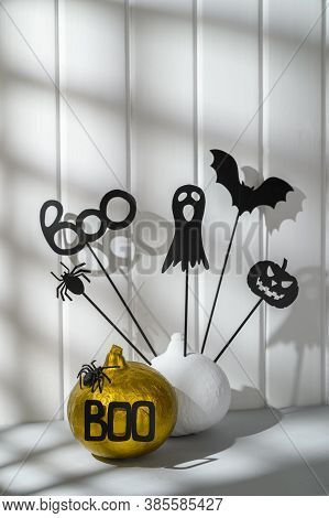 Halloween Home Decorations. Painted White And Gold Pumpkins With Scary Black Halloween Objects On A