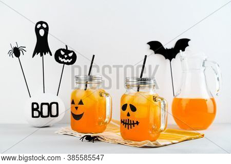 Iced Pumpkin Cocktails In Glass Jars Decorated With Scary Faces On A White Table. Diy Halloween Part