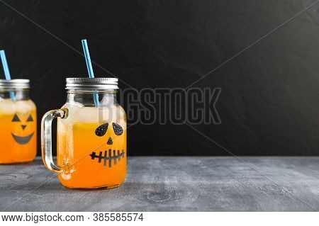 Iced Pumpkin Cocktails In Glass Jars Decorated With Scary Faces On The Chalkboard, Black Background.