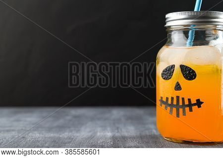 Iced Pumpkin Cocktail In Glass Jar Decorated With Scary Face On The Chalkboard, Black Background. Ha