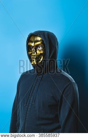Portrait Of A Man In A Skull Mask With A Hood On A Blue Background. Halloween Party Costume. Vertica