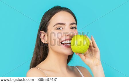 Stomatology Concept. Woman With Perfect Smile Holding Apple, Blue Background. Woman Eat Green Apple.