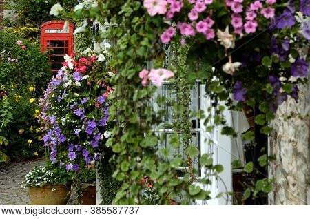 Red Telephone Booth With Flowers On The Wall