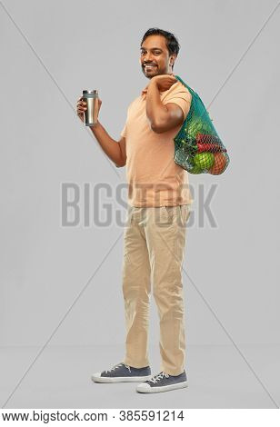 sustainability, consumerism and eco friendly concept - happy smiling indian man holding green reusable string bag for food shopping and tumbler or thermo cup on grey background