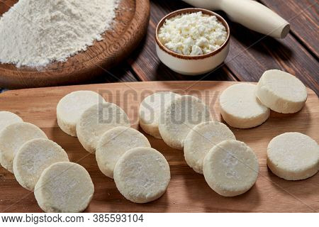 raw cottage cheese pancakes on the wooden board