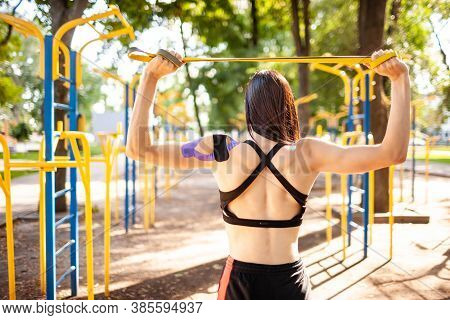 Brunette Muscular Woman Posing With Fitness Resistance Band In Park, Sports Ground On Background. Ba