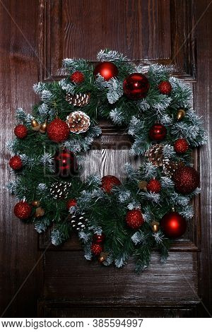 Christmas Wreaths And Decoration On The Doors Of The House. Christmas Wreath On Wooden Door Decorati