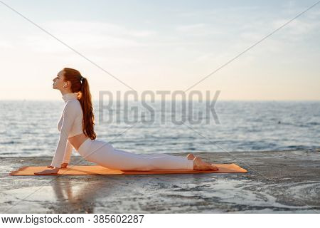 Image of redhead young girl in earphones doing exercise while working out on promenade at sunrise