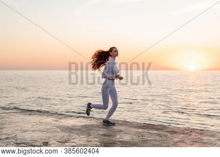 Image of redhead focused girl in earphones running while working out on promenade at sunrise