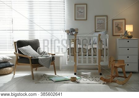 Baby Room Interior With Crib, Armchair And Rocking Horse. Idea For Design