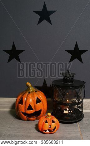 Pumpkin And Jack O'lantern Against A Black Wall With Stars. Lantern With Candles