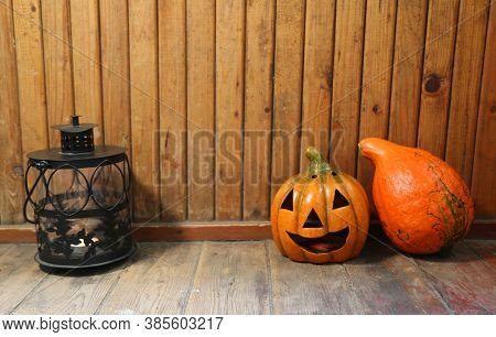 Pumpkin And Jack O'lantern On The Background Of Old Wooden Wall. Lantern With Candles