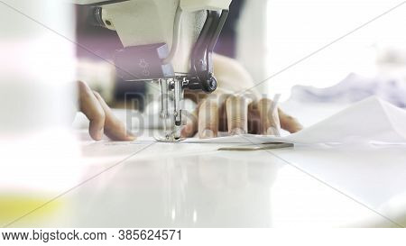 Female Hands Sewing White Sewing Machine, Top View Shot. Female Fingers Sewing White Cloth On White