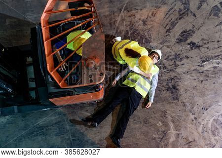 Asian worker do Cardiopulmonary Resuscitation CPR after warehouse manager lying down on warehouse floor after accident from forklift. Using for safety first and business insurance concept. Top view.
