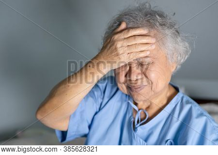 Asian Senior Or Elderly Old Lady Woman Patient Headache While Sitting On Bed In Nursing Hospital War