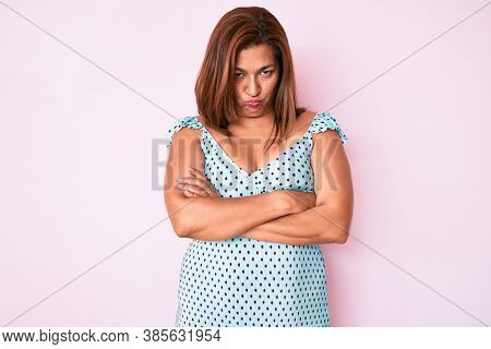 Middle age brunette hispanic woman wearing summer dress skeptic and nervous, disapproving expression on face with crossed arms. negative person.