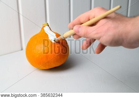 Halloween Concept. A Male Hand With A Paintbrush Paints An Orange Pumpkin White On The Table. Horizo