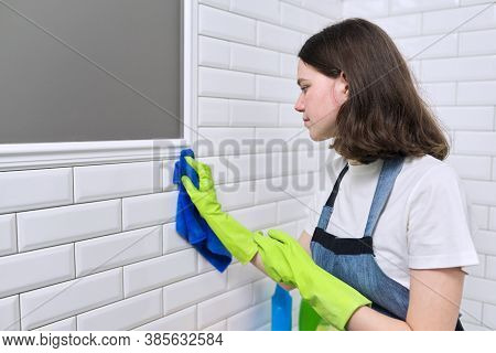 Girl Doing Cleaning In Bathroom. Teenager In Apron Gloves With Detergent And Rag Washing White Tile