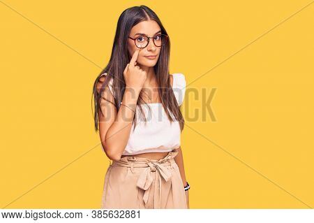 Young hispanic woman wearing casual clothes and glasses pointing to the eye watching you gesture, suspicious expression