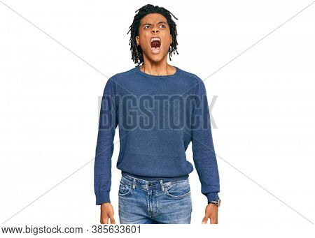 Young african american man wearing casual winter sweater angry and mad screaming frustrated and furious, shouting with anger. rage and aggressive concept.