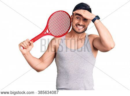 Young handsome man holding tennis racket stressed and frustrated with hand on head, surprised and angry face