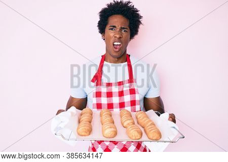 Handsome african american man with afro hair wearing baker uniform holding homemade bread in shock face, looking skeptical and sarcastic, surprised with open mouth