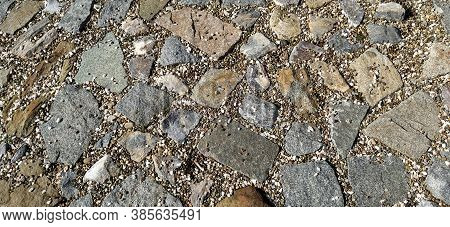 Pavement Paved With Uneven Natural Gray And Brown Stones. Between Crushed Cobblestones There Are Sma