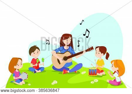 Children And Teacher Sitting On Grass And Playing Musical Instruments Together. Kids Enjoying Outdoo
