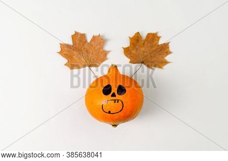 Top View Of Halloween Pumpkin With Painted Face And Horns From Autumn Leaves On Gray Background. Cop