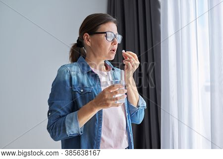 Mature Middle-aged Woman In Casual Clothes At Home Holding Pill And Glass Of Fresh Water. Headaches,