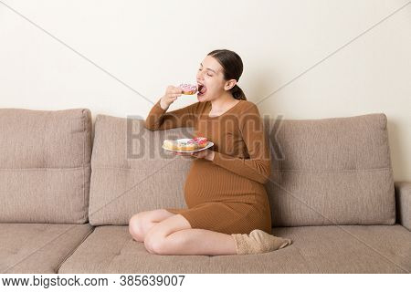 Pregnant Woman Enjoys Eating Different Donuts Resting On The Sofa. Unhealthy Desserts During Pregnan