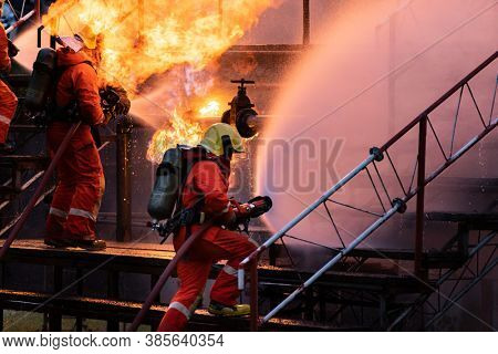 Firefighter team using water fog type fire extinguisher to fighting with the flame from oil pipeline leak and explosion on oil rig and natural gas station. Firefighter and industrial safety concept.