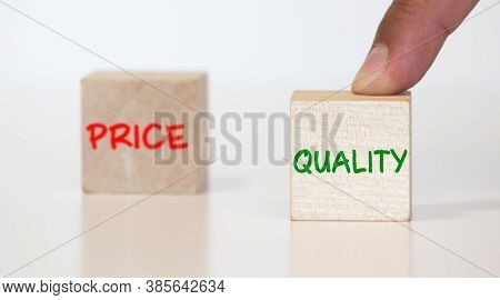 Symbol For Choosing Quality Instead Of A Cheap Price. Two Hands Hold Two Dice With The Words Quality