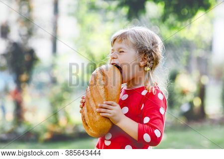 Little Toddler Girl Holding Big Loaf Of Bread. Funny Happy Child Biting And Eating Healthy Bread, Ou