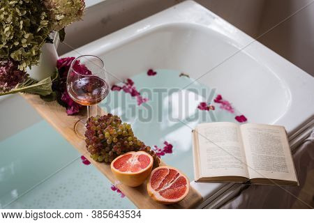 Bath Tub With A Tray With Grapefruit Slices, Bunch Of Grapes, A Glass Of Wine And A Book