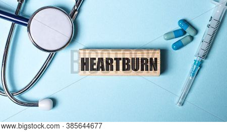 Heartburn Is Written On A Wooden Block On A Blue Background Near The Stethoscope, Syringe And Pills.