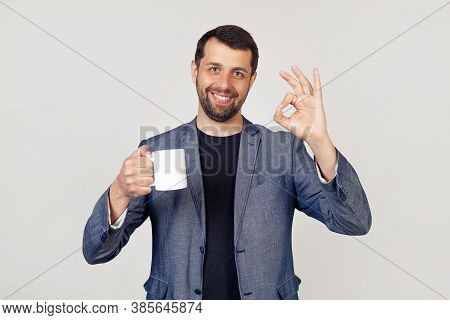 Young Businessman With A Smile, A Man With A Beard In A Jacket, Holding A Cup Of Coffee And Showing