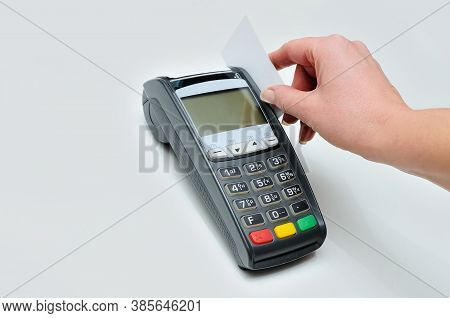 The Girl Holds In Hand A Credit Card In Front Of The Terminal On White Background. A White Credit Ca