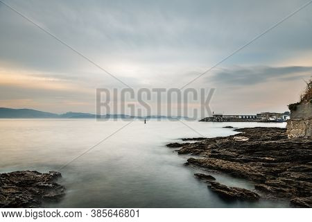 Rocks And Small Lighthouse On A Calm Cloudy Evening In The Rias Baixas In Galicia, Spain. Long Expos