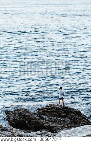 Portonovo, Spain - August 7, 2020: Lonely Fisherman Fishing By The Sea On A Calm Clear Evening In Th
