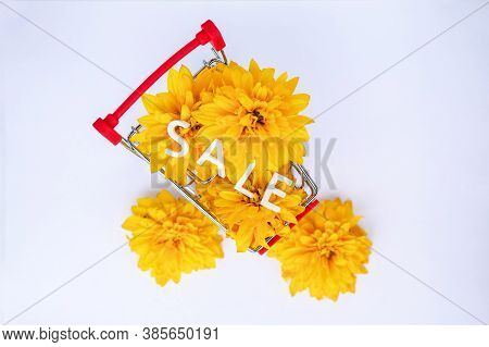 Small Red Metal Shopping Cart For Shopping In The Store With A Bouquet Of Yellow Flowers, Buds On A