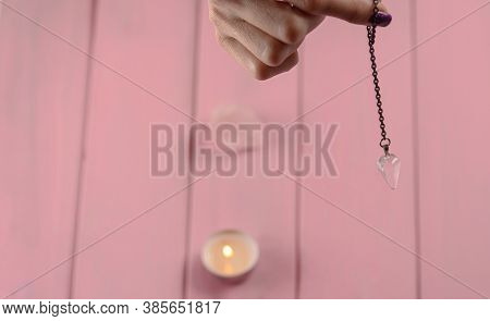 Arm Of A Dowser With Hand-held Pendulum On A Chain With A Natural Crystal On A Background Of Pink Wo